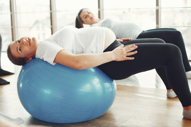 woman-in-white-t-shirt-and-black-leggings-stretching-on-blue-3984355